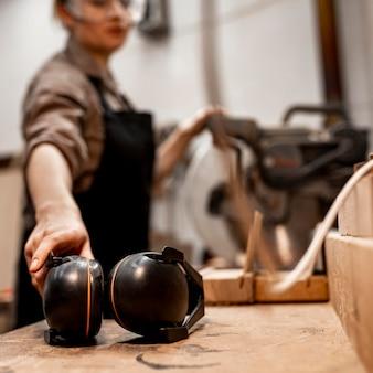 Vrouwelijke timmerman in de studio met koptelefoon