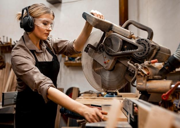 Vrouwelijke timmerman met behulp van elektrische zaag in de studio