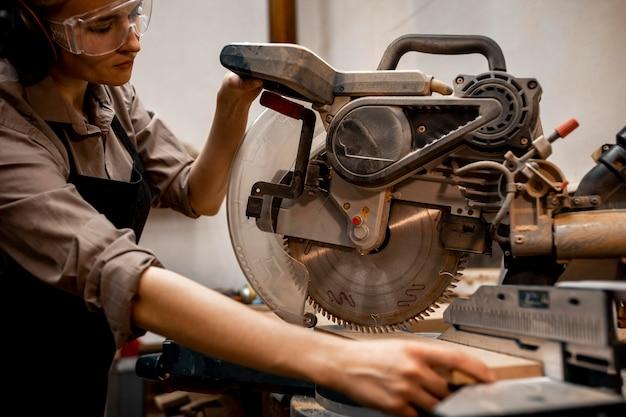 Vrouwelijke timmerman met behulp van elektrische zaag