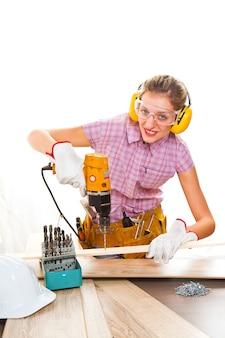 Vrouwelijke timmerman op het werk met behulp van handboormachine