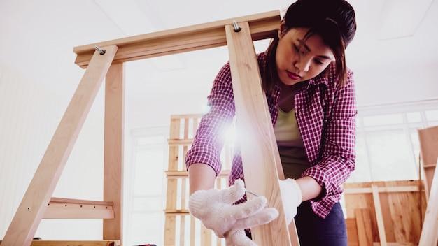 Vrouwelijke timmerman schroeven stukken plank samen op site.
