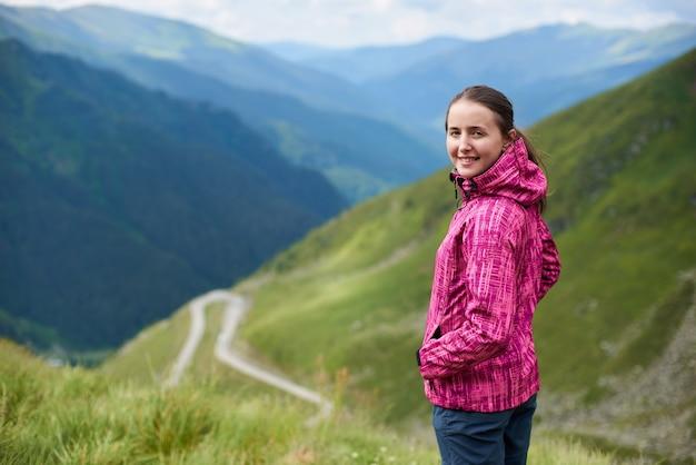 Vrouwelijke toerist bovenop heuvel in de bergen