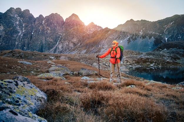 Vrouwelijke toerist die bij hoge tatra bij gouden zonsondergang, slowakije wandelen