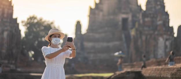 Vrouwelijke toerist die chirurgisch masker draagt die tempel wat chaiwatthanaram bezoekt