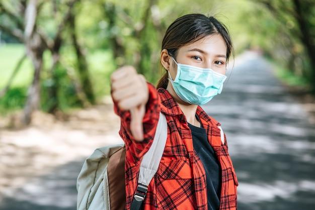 Vrouwelijke toerist die een rugzak en duimen op de weg draagt.