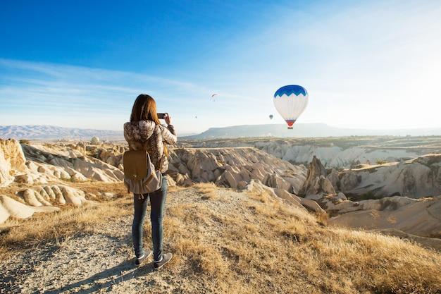 Vrouwelijke toerist die foto's van hete luchtballon in cappadocia