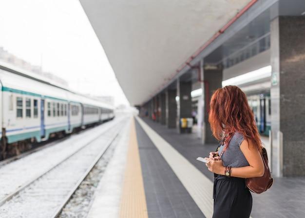 Vrouwelijke toerist die op trein wacht