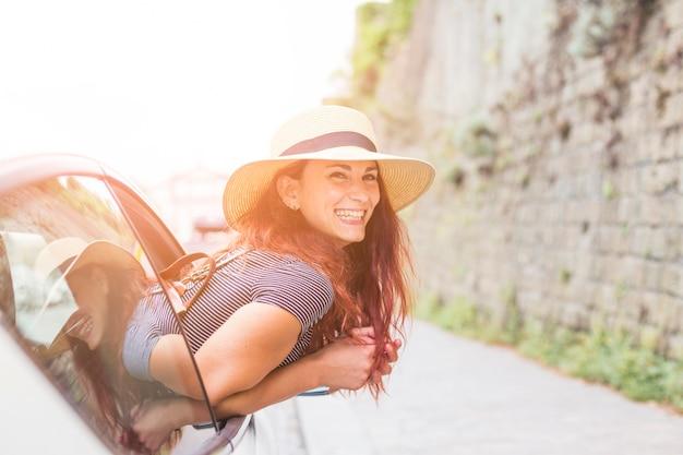 Vrouwelijke toerist die uit autoraam kijkt