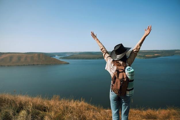 Vrouwelijke toerist die zich op bergpiek bevindt dichtbij bakota-baai