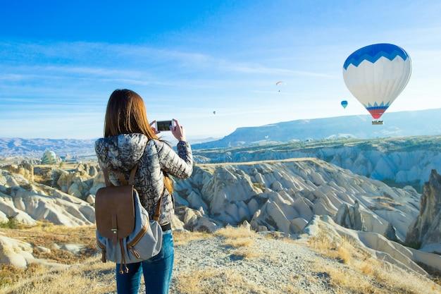Vrouwelijke toerist fotograferen van luchtballonnen in cappadocië