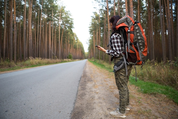 Vrouwelijke toerist in een geruit overhemd met een oranje grote rugzak in de buurt van een snelweg in het bos met een smartphone in de hand. navigatie, satellietkaarten, communicatie, binnenlands toerisme. backpacker, avontuur