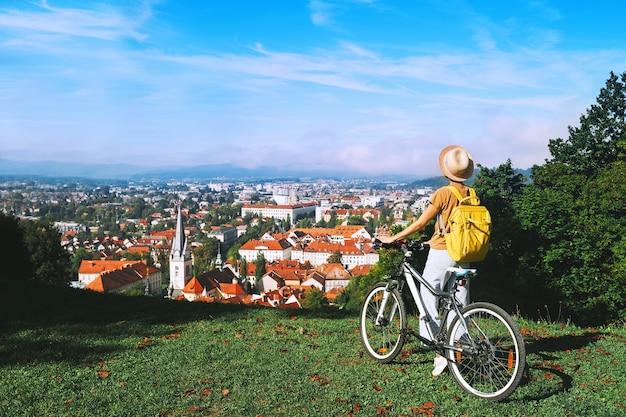 Vrouwelijke toerist kijkt naar panoramisch uitzicht met rode daken van ljubljana vanuit city castle
