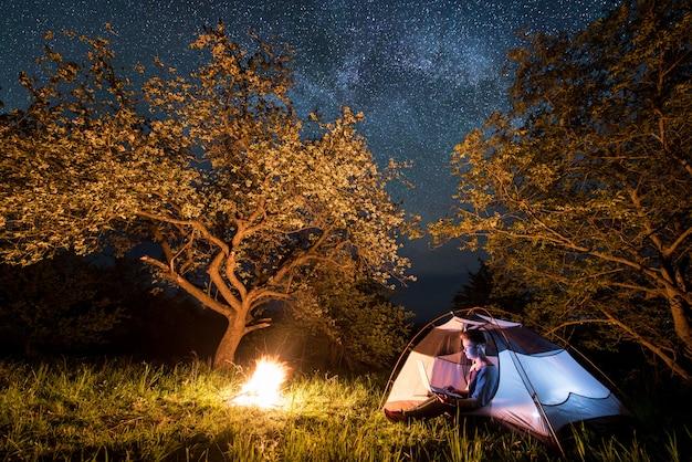 Vrouwelijke toerist met behulp van haar laptop op de camping in de nacht. vrouw zitten in de buurt van kampvuur en tent onder bomen en prachtige nachtelijke hemel vol sterren en melkweg