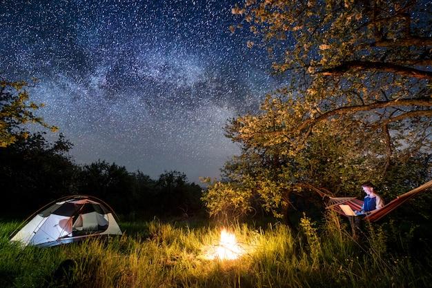 Vrouwelijke toerist met behulp van haar laptop op de camping in de nacht. vrouwenzitting in de hangmat dichtbij kampvuur en tent onder bomen en mooie nachthemel vol sterren en melkweg