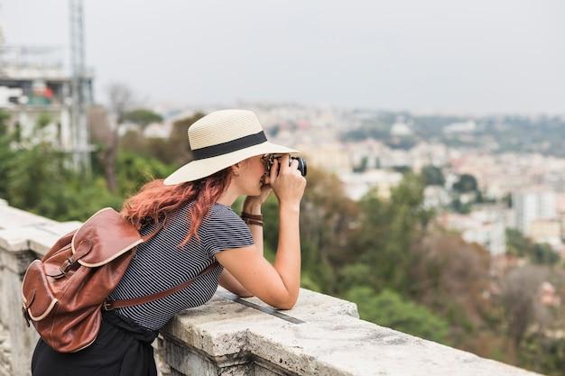 Vrouwelijke toerist met camera op balkon