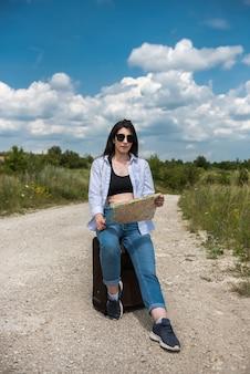 Vrouwelijke toerist met een kaart lopen op een weg op zonnige zomerdag. vakantie concept