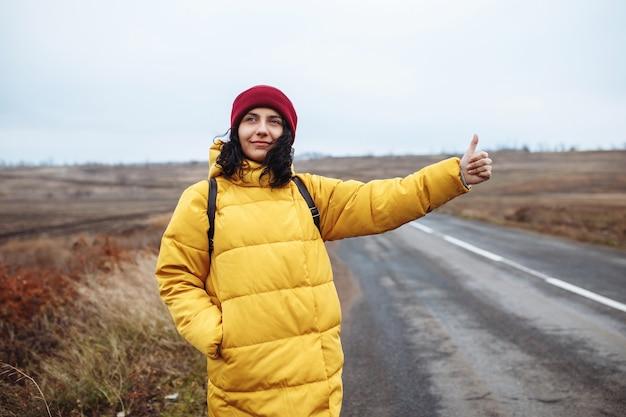 Vrouwelijke toerist met een rugzak die een gele jas en een rode hoed draagt, vangt een auto op de weg.