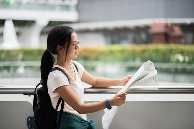 Vrouwelijke toerist met stadskaart die bestemming kijkt