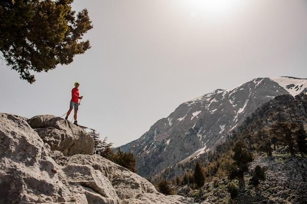 Vrouwelijke toerist met wandelingsapparatuur in bergen