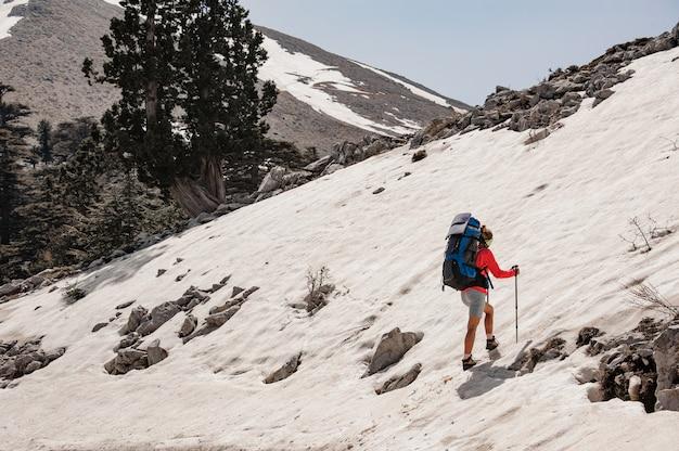 Vrouwelijke toerist met wandelingsapparatuur in sneeuwbergen