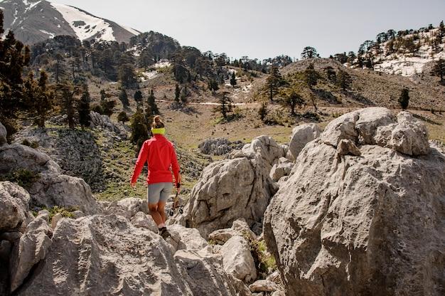 Vrouwelijke toerist met wandelingsuitrusting onder stenen