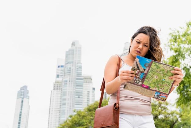 Vrouwelijke toerist met zak op schouders die kaart in de stad onderzoeken