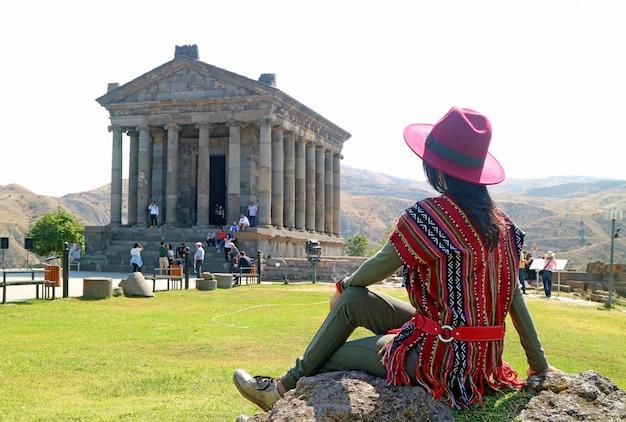 Vrouwelijke toerist onder de indruk van de prachtige architectuur van de tempel van garni, armenië