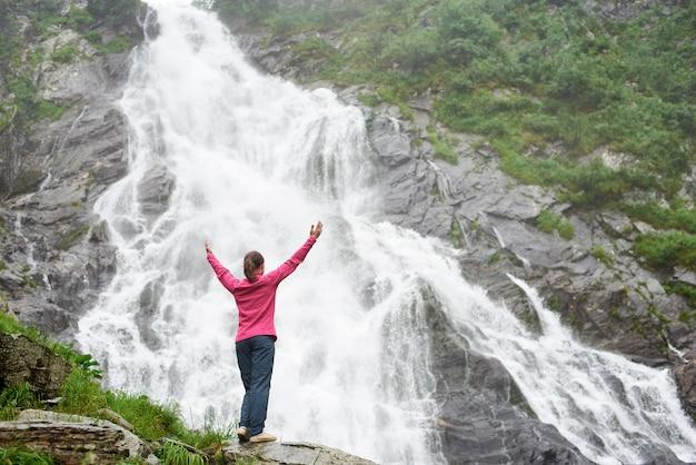 Vrouwelijke toerist opheffende handen omhoog genietend van prachtig adembenemend uitzicht op waterval