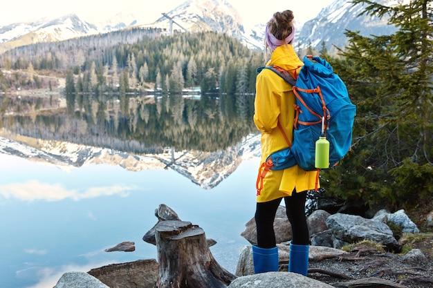 Vrouwelijke toerist staat aan de oever van een prachtig bergmeer, geniet van majestueuze landschappen en natuur