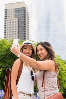 Vrouwelijke toerist twee met hun rugzak die selfie op cellphone in openlucht nemen