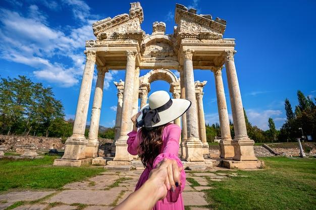 Vrouwelijke toeristen houden de hand van de man vast en leiden hem naar de oude stad aphrodisias in turkije.
