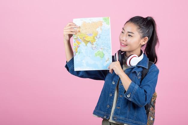 Vrouwelijke toeristen in de studio op een roze achtergrond.