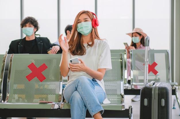 Vrouwelijke toeristen luisteren naar muziek en dragen maskers om virussen te voorkomen terwijl ze wachten om aan boord van het vliegtuig te gaan