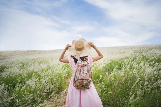 Vrouwelijke toeristen staan en houden een hoed in de uitgestrekte graslanden
