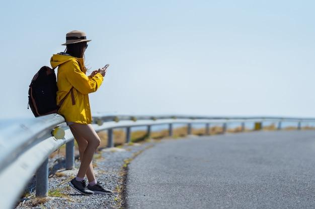 Vrouwelijke toeristen wacht ze op de bus. ze gebruikt de auto-app.