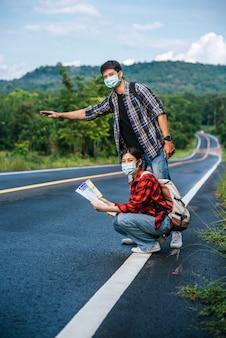 Vrouwelijke toeristen zitten en kijken naar de kaart, mannelijke toeristen die doen alsof ze liften. beiden dragen maskers en staan aan de kant van de weg.