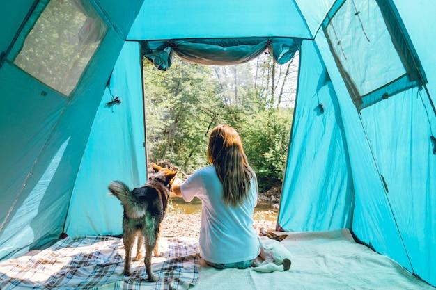 Vrouwelijke toeristenreiziger in kamp in een bos met haar honden samen op een natuurreis, vriendschapsconcept, openluchtactiviteiten, reizen met een huisdier.