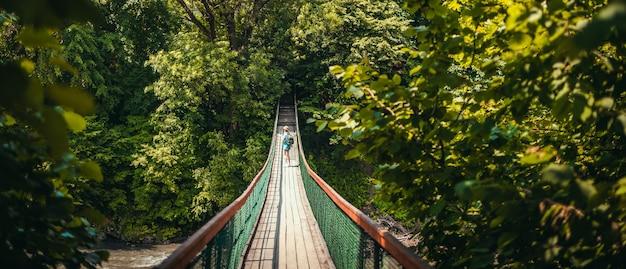 Vrouwelijke toeristenreiziger loopt op een hangende brug in het midden van het bergbos, verkent de natuur in een natuurlijke omgeving. wandelen of trekking concept levensstijl