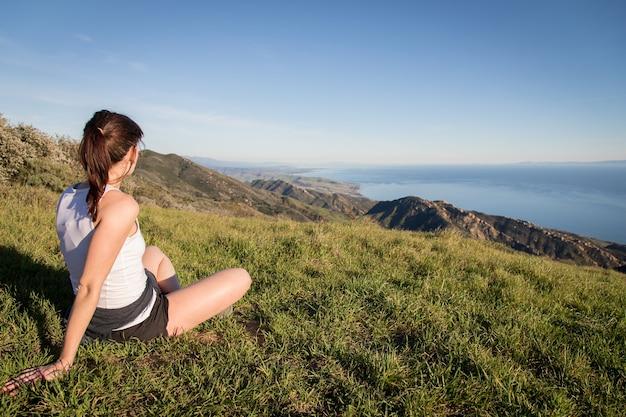 Vrouwelijke toeristenzitting bovenop de gaviota peak-wandelingssleep die de kust van californië overzien