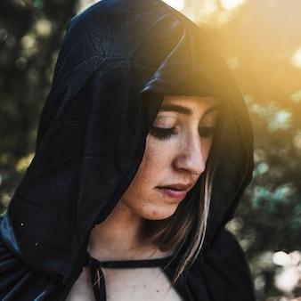 Vrouwelijke tovenaar in zwarte kaap in zonnig bos