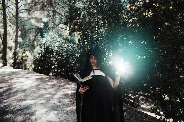 Vrouwelijke tovenaar praktizerende hekserij in zonnig bos