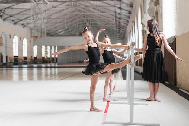 Vrouwelijke trainer die ballerinameisjes bekijken die hun been op bar uitrekken