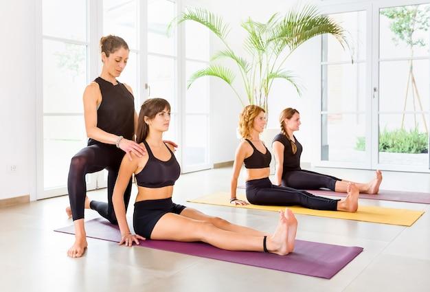 Vrouwelijke trainer die jonge vrouw helpt door dandasana-yogapositie aan te passen. yogales die binnenshuis oefenen in een ruime kamer met lichte ramen