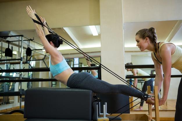 Vrouwelijke trainer meewerkende vrouw met uitrekkende oefening