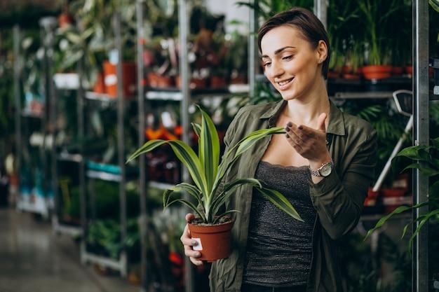Vrouwelijke tuinman bij plantenhuis met planten en bloemen