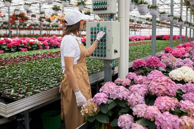 Vrouwelijke tuinman die moderne apparatuur gebruikt om bloemen water te geven