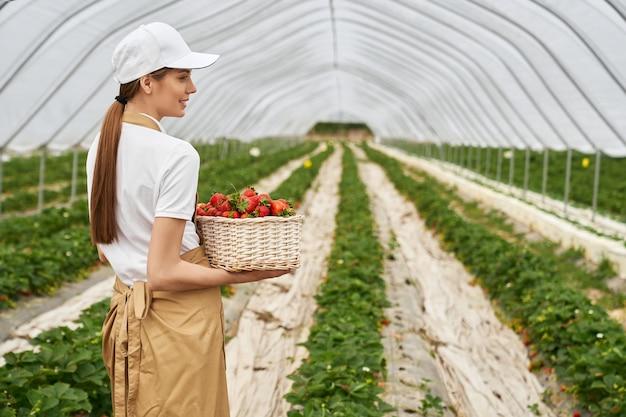 Vrouwelijke tuinman dragende mand met verse aardbeien