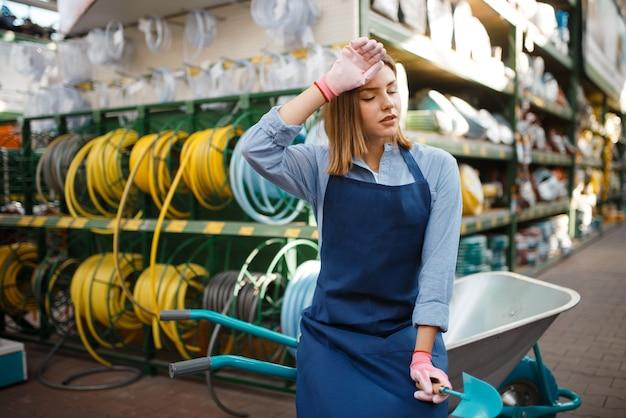 Vrouwelijke tuinman in schort met tuinkar in winkel voor tuinlieden. vrouw verkoopt apparatuur in de winkel voor bloementeelt, bloemistverkoop