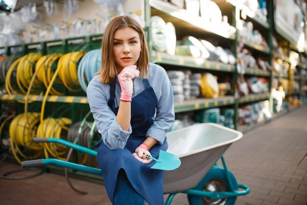 Vrouwelijke tuinman in schort met tuinkar in winkel voor tuinlieden. vrouw verkoopt apparatuur in de winkel voor de bloementeelt, de verkoop van bloemistinstrumenten