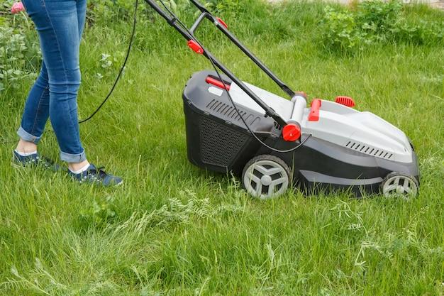 Vrouwelijke tuinman in spijkerbroek werkt met grasmaaier in de tuin in zomerdag. maaier gras apparatuur. maaigereedschap voor tuinmanonderhoud.